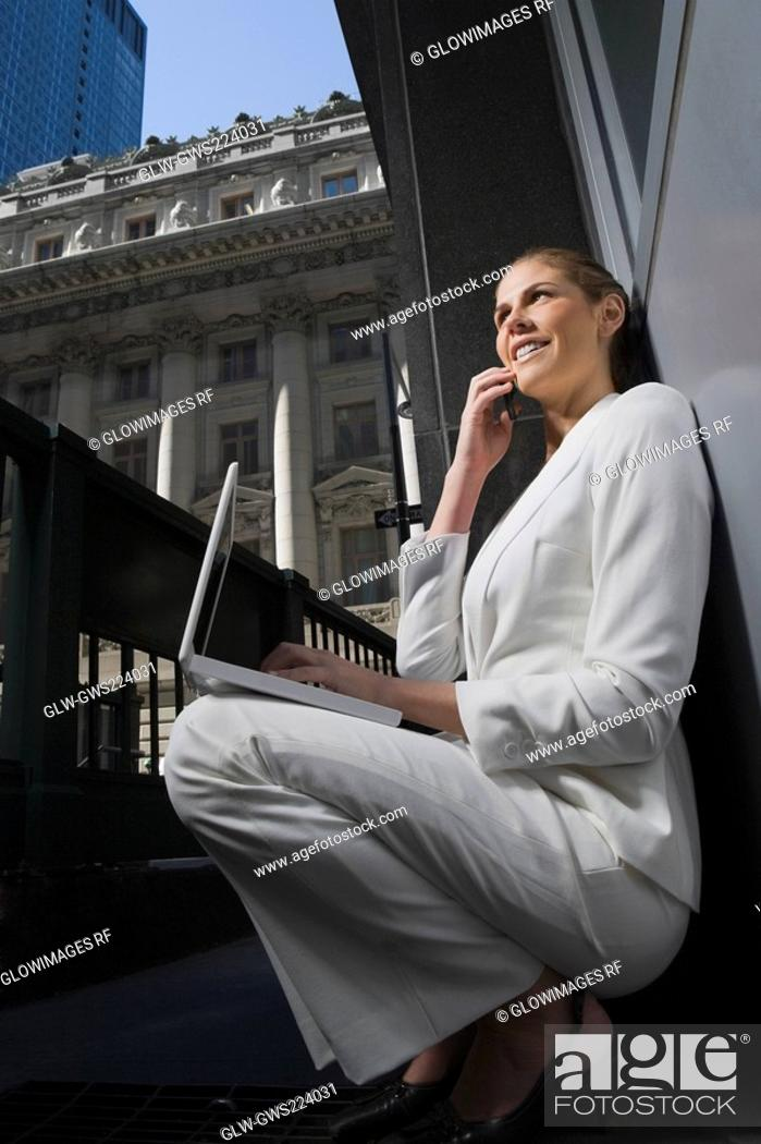Stock Photo: Side profile of a businesswoman talking on a mobile phone and using a laptop.