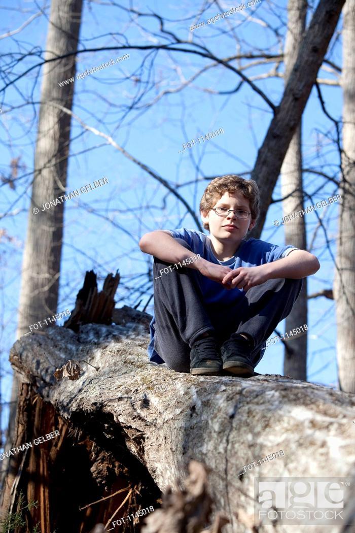 Stock Photo: Boy sitting on broken tree trunk.