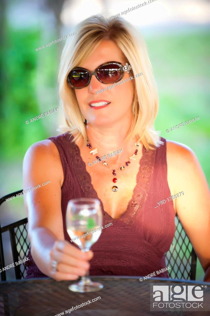 Stock Photo: Outdoot portrait of 45 years old woman sitting relaxed on a table.