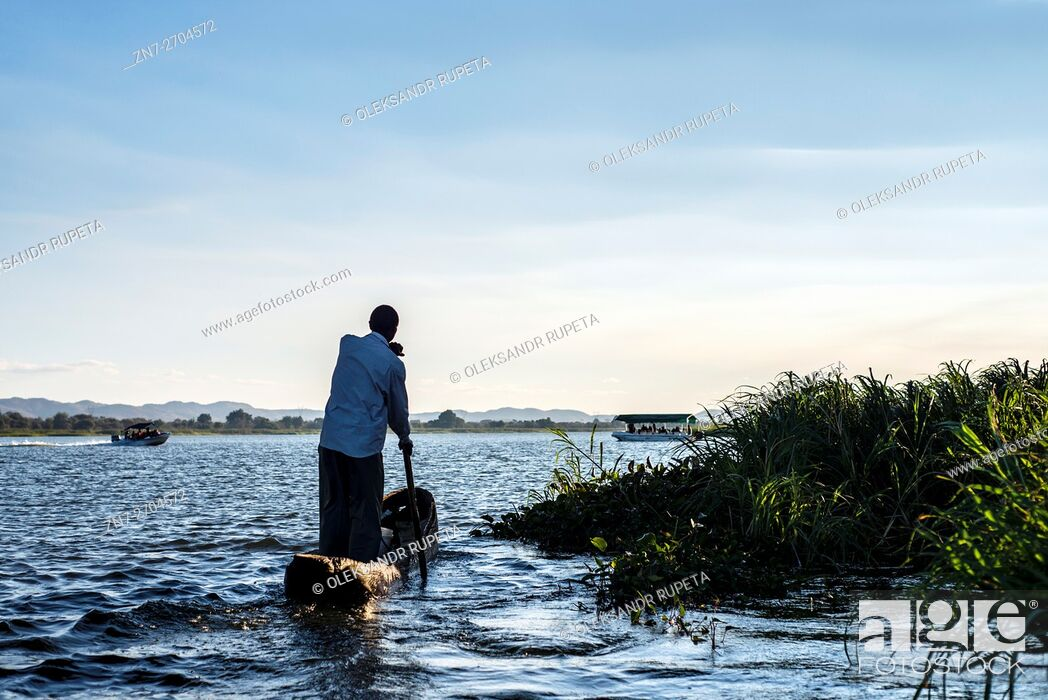 Stock Photo: Man rowing in a handmade wooden kayak on Kafue river, Kafue, Zambia.