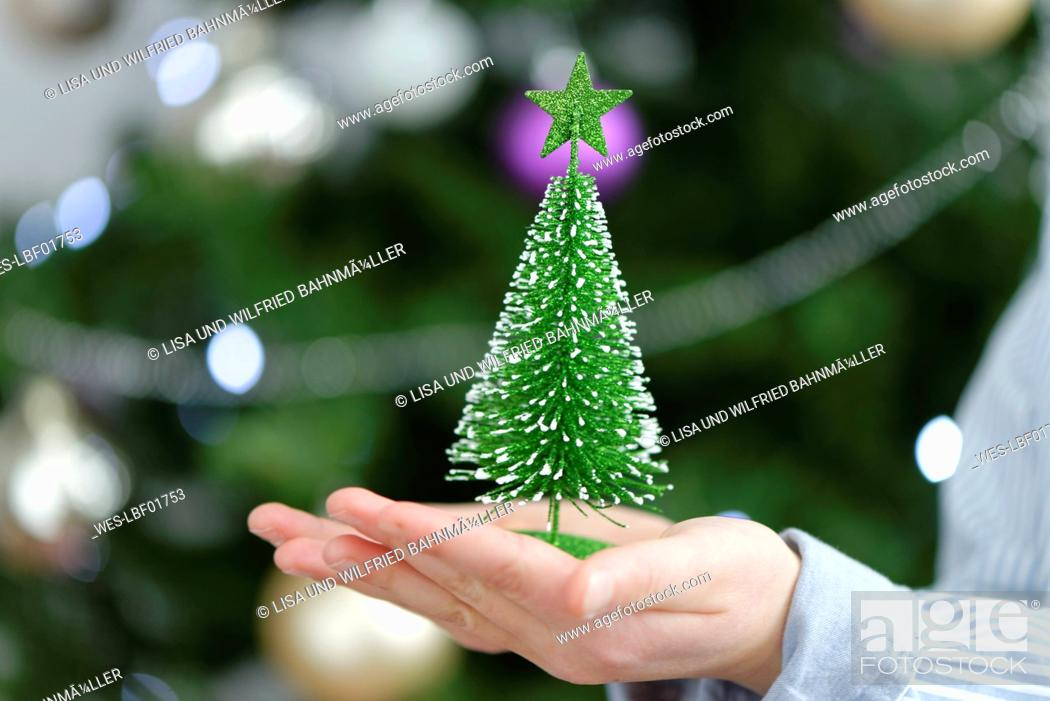 Stock Photo: Little boy holding a toy Christmas tree, close up.