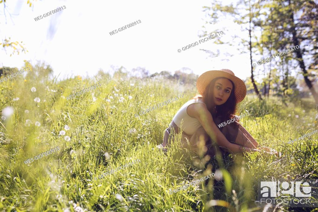 Stock Photo: Young woman wearing straw hat sitting on a meadow.