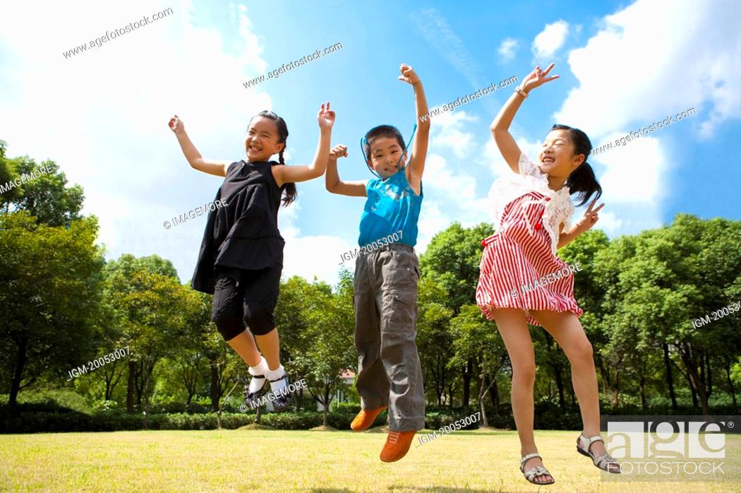 Stock Photo: Three children jumping in mid-air with arms outstretched and smiling.