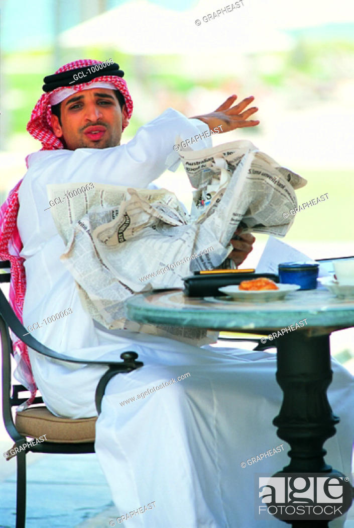 Stock Photo: Arab businessman screwing up newspaper in anger.