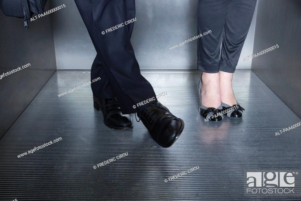 Stock Photo: Man and woman standing in elevator, man moving foot toward woman's foot.
