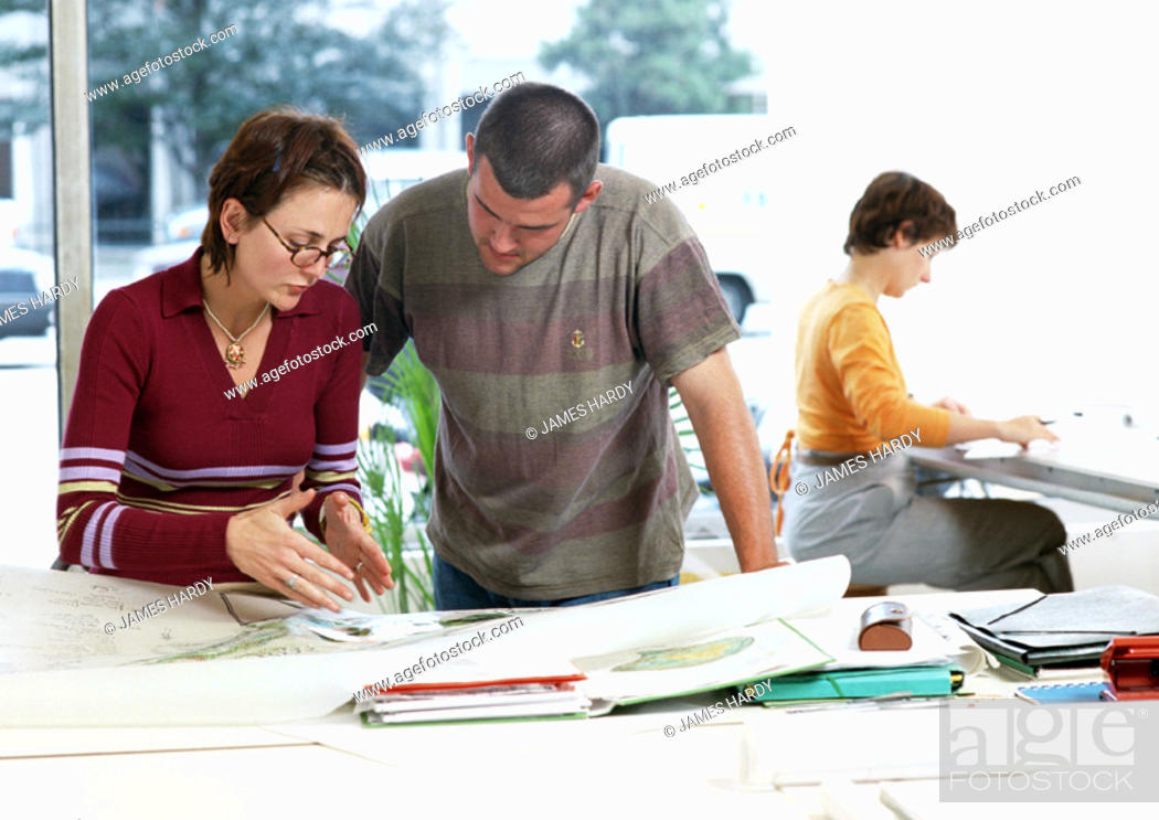 Stock Photo: Woman and man looking at plans, woman sitting in background.