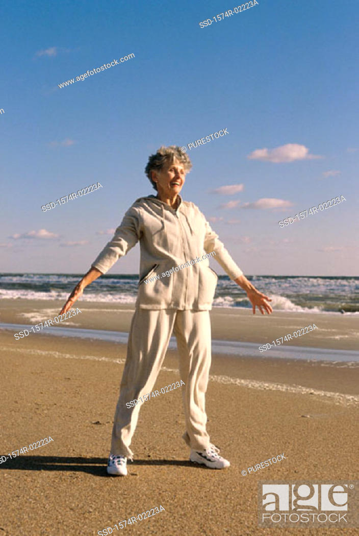 Stock Photo: Senior woman exercising on the beach.