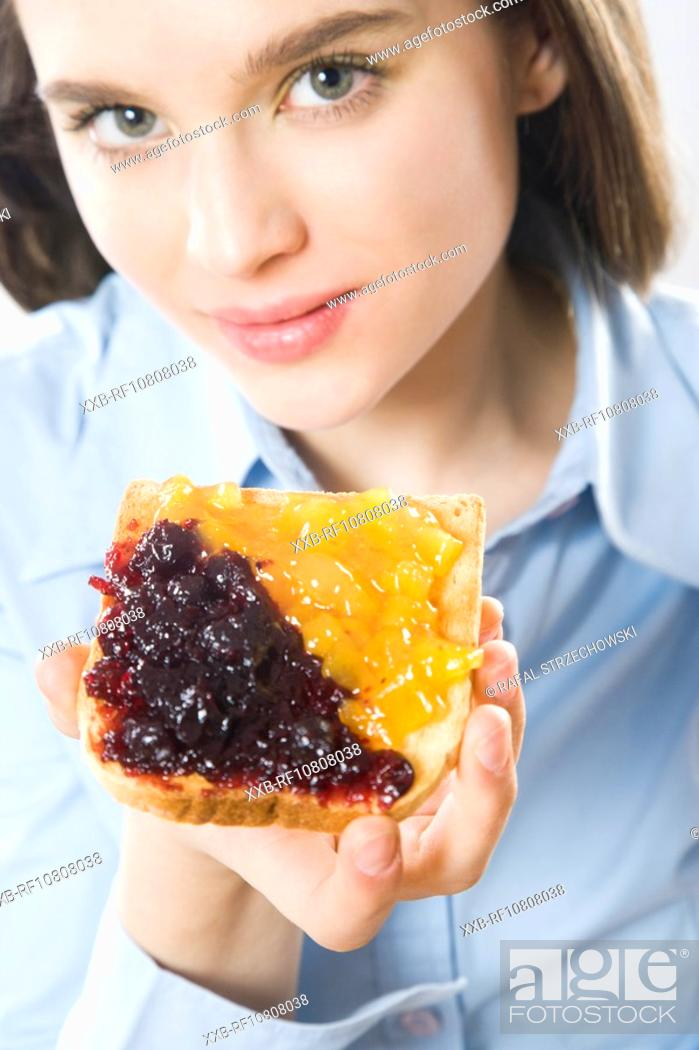 Stock Photo: Young woman eating toast with jam.