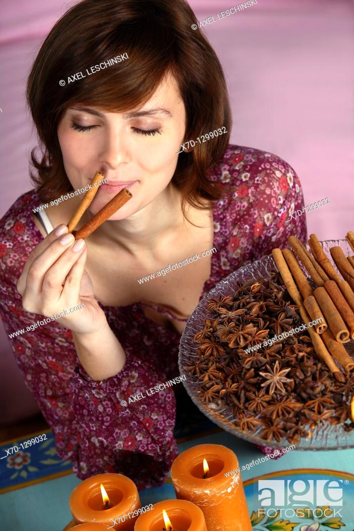 Stock Photo: young brunette woman holding winter spices in hands.
