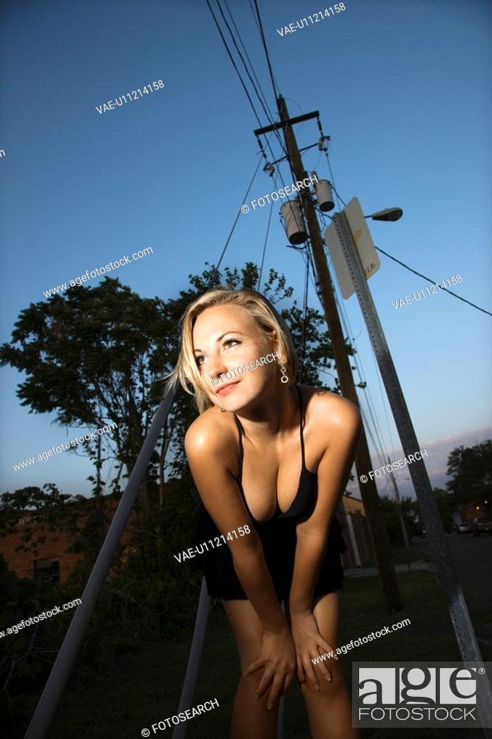 Stock Photo: Caucasian mid-adult blonde woman wearing little black dress showing cleavage posing in front of power lines.