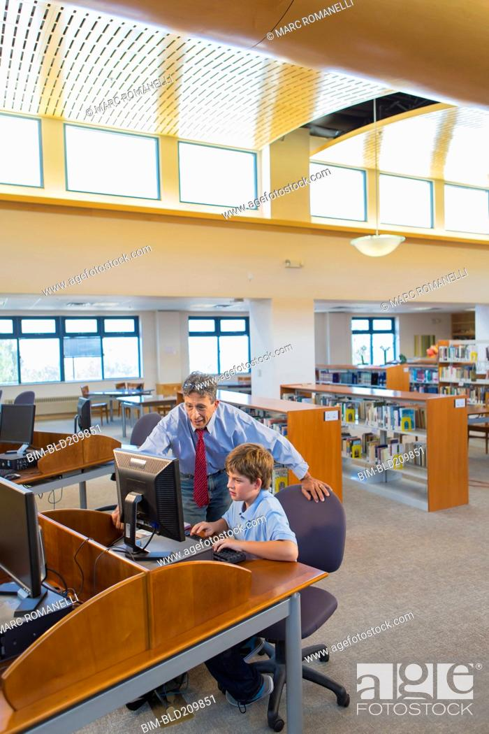 Stock Photo: Teacher and student working at computer in library.
