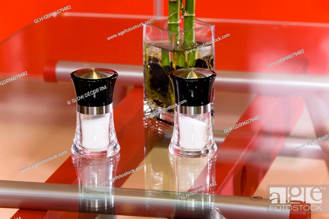 Photo de stock: Salt shakers with a lucky bamboo on a table.