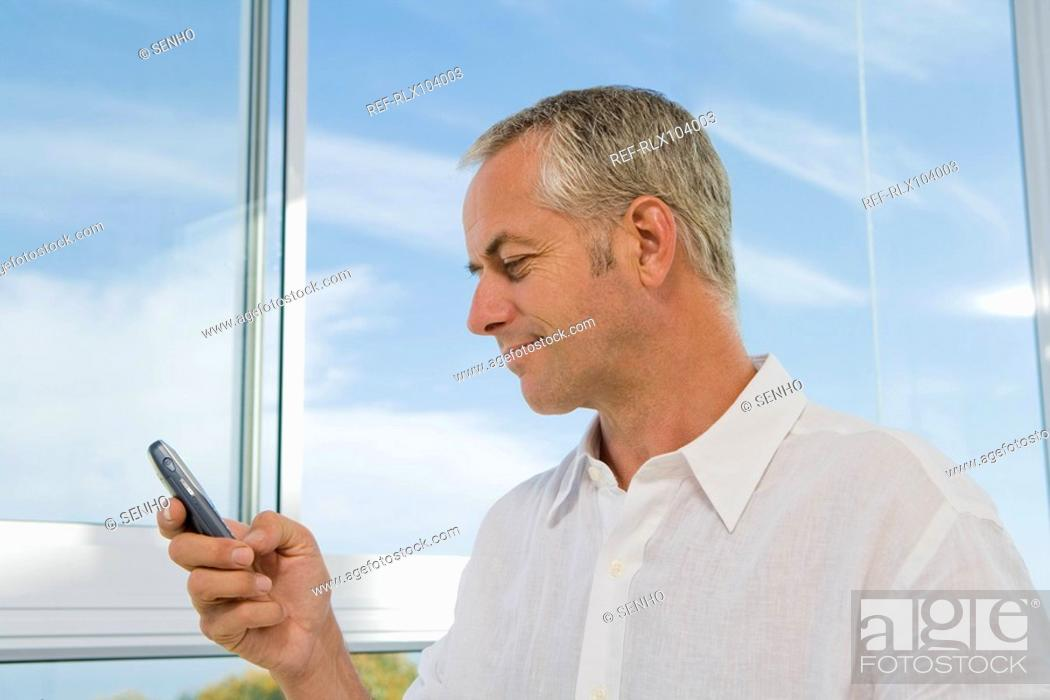 Stock Photo: Mature man at window using cell phone, looking at display.