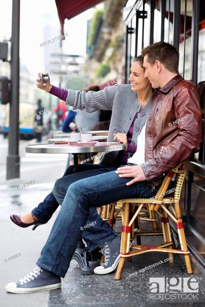 Stock Photo: Young couple sitting at table outside cafe, woman taking photo, Paris France.