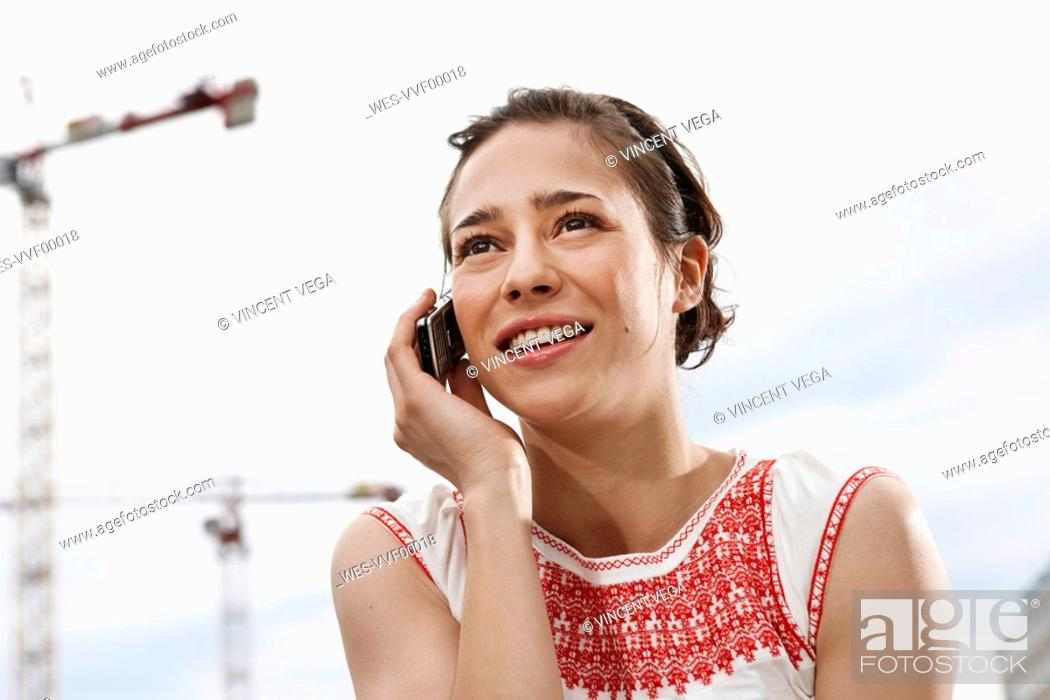 Stock Photo: Germany, Berlin, Young woman using mobile phone, portrait, close-up.
