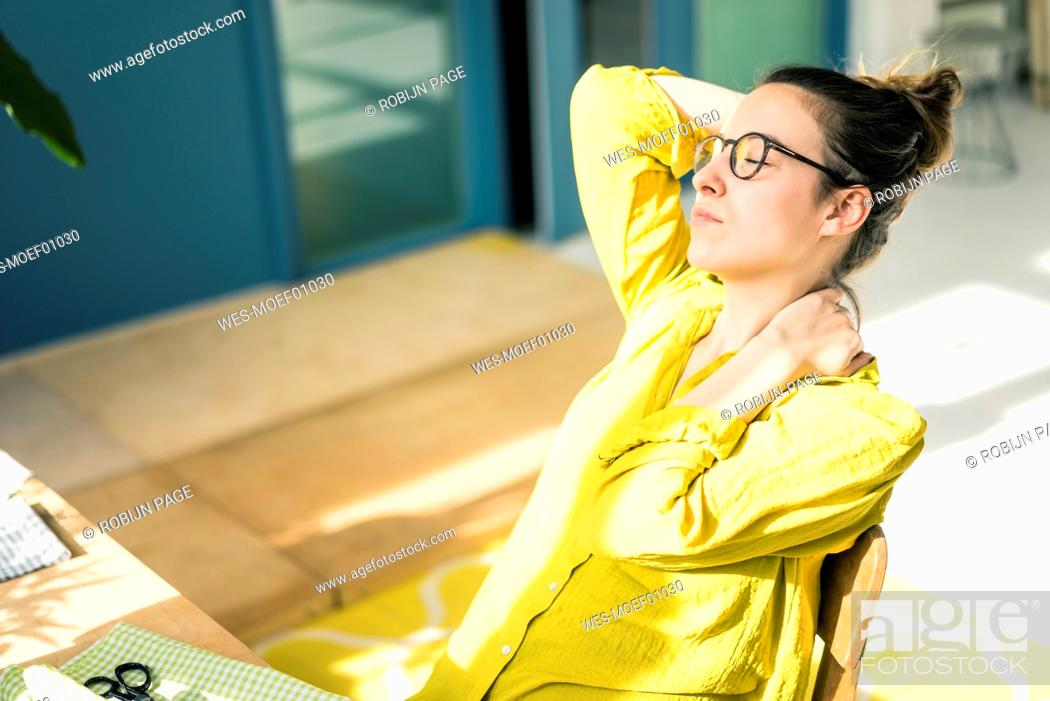Stock Photo: Young fashion designer relaxing at desk in her studio.
