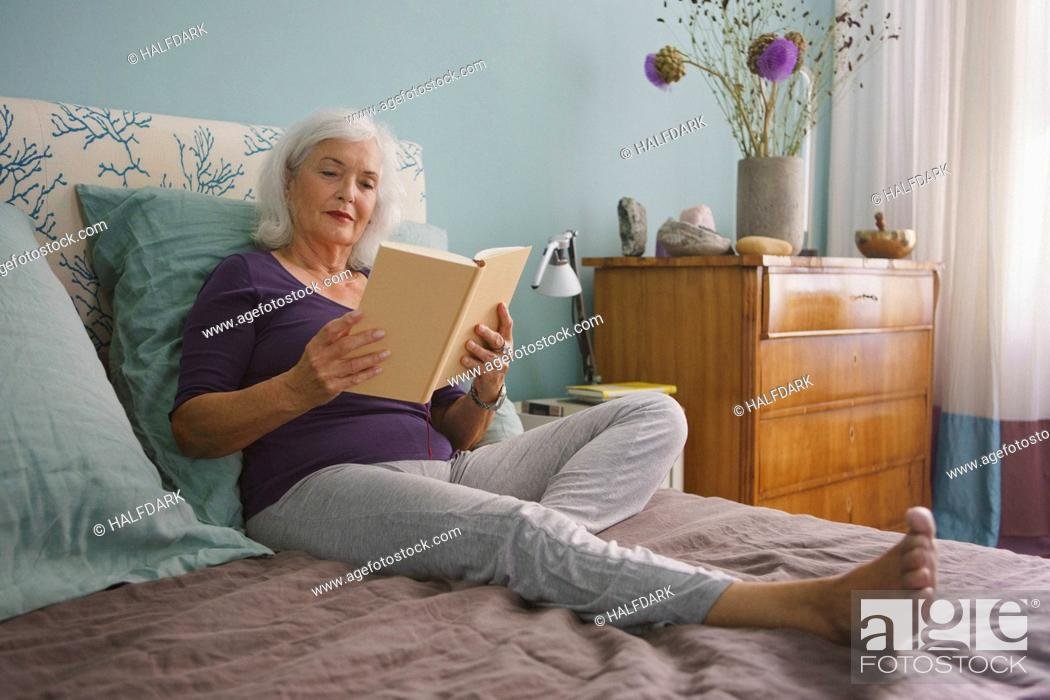 Stock Photo: Senior woman reading book on bed.