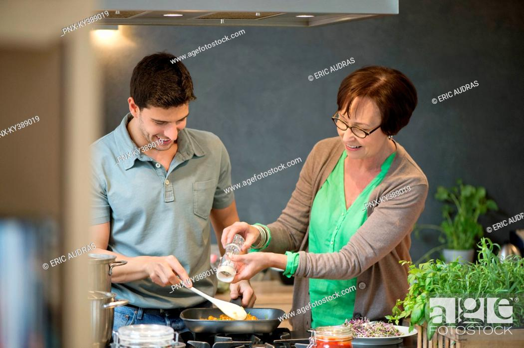 Stock Photo: Woman assisting her son to cook food.