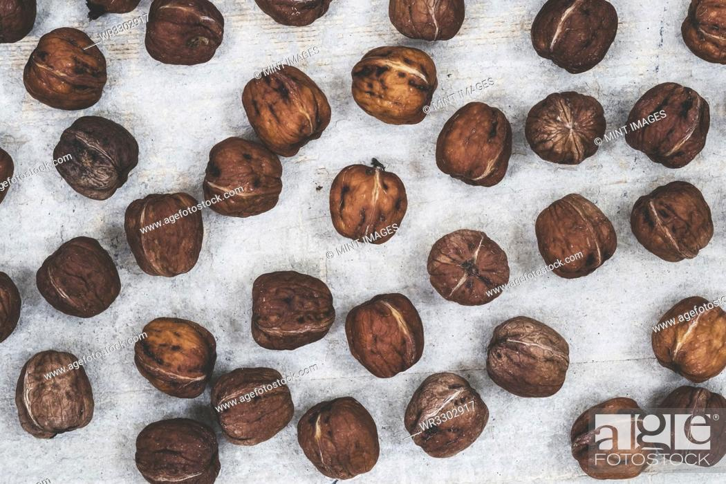 Stock Photo: High angle close up of fresh walnuts on grey background.