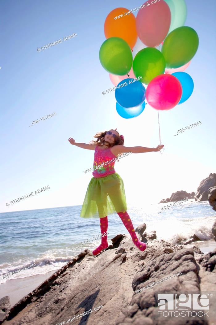 Stock Photo: little girl holding balloons and jumping while on the rocks at the ocean.
