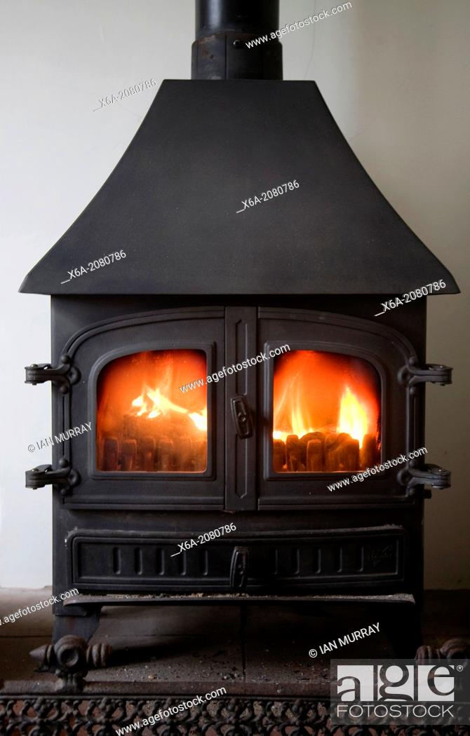 Stock Photo: Warm flames of cosy multi-fuel burner fire stove in domestic home, UK.