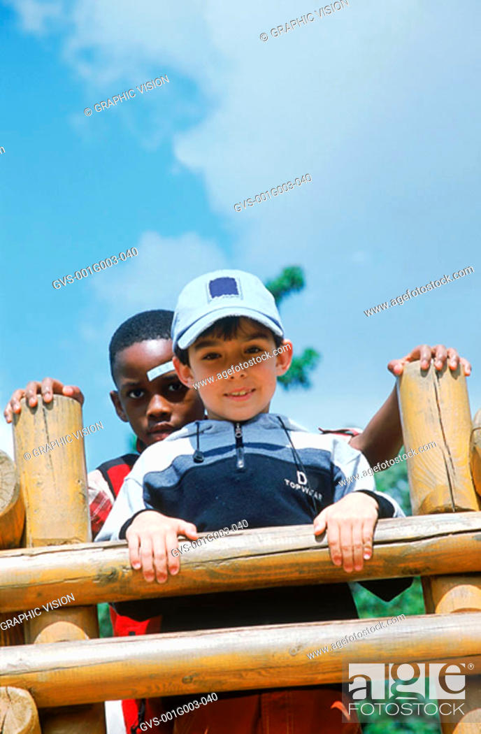 Stock Photo: Young boys standing against wooden fence smiling.