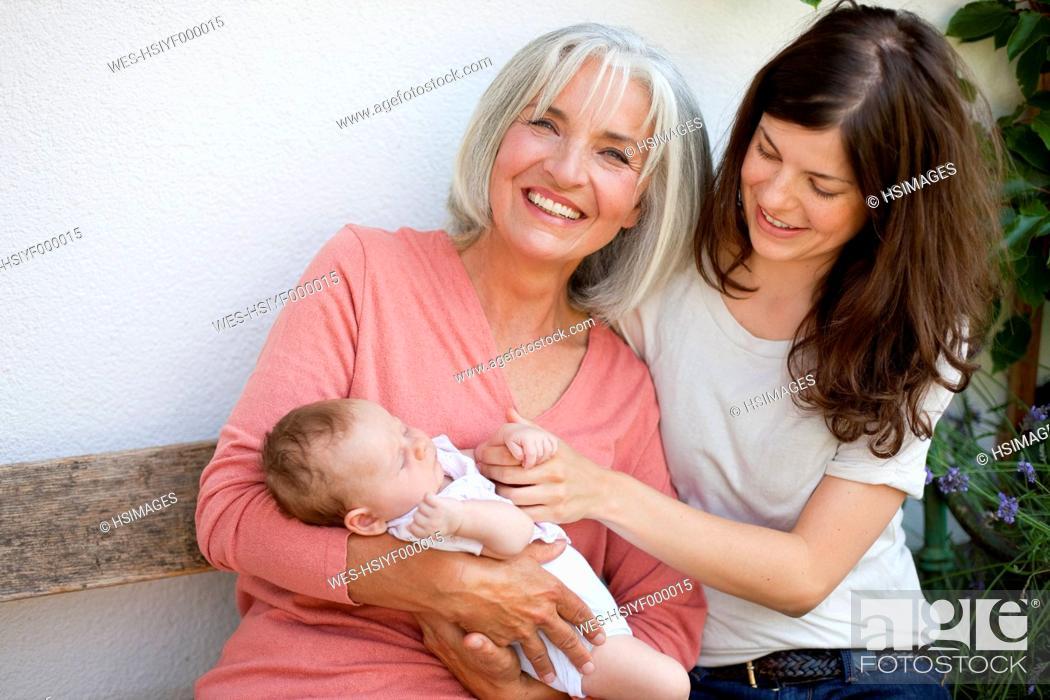 Stock Photo: Germany, Bavaria, Three generations sitting together, smiling.