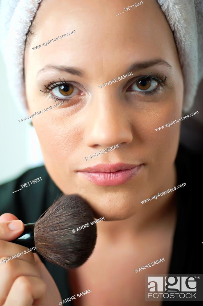 Stock Photo: Close up of woman's face putting on makeup.