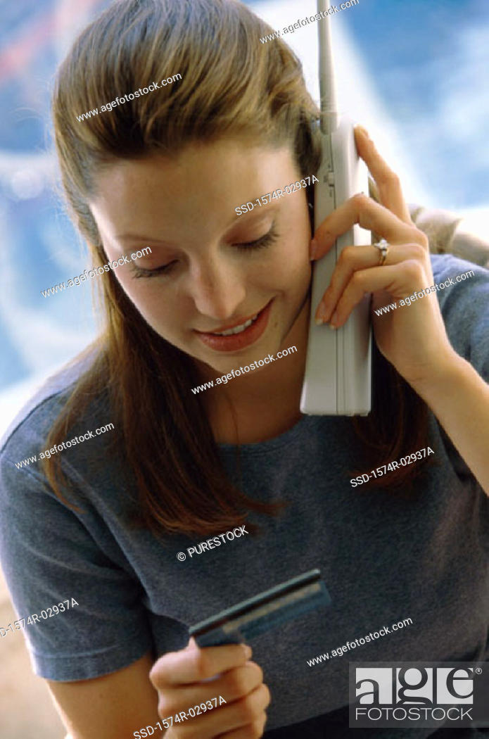 Stock Photo: Young woman using a cordless phone holding a credit card.