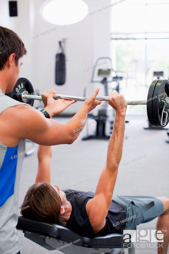 Stock Photo: Man spotting friend lifting barbell in gymnasium.