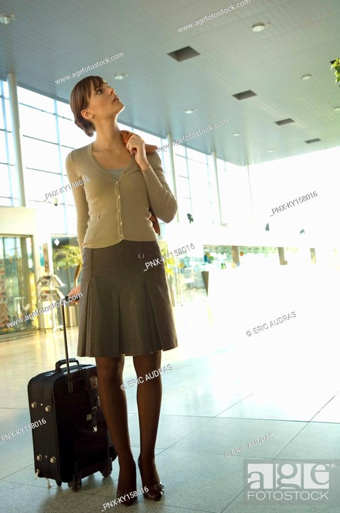 Stock Photo: Businesswoman standing with her luggage at an airport lounge.