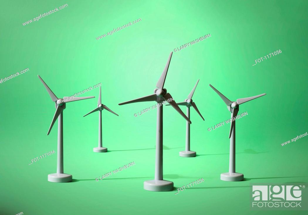 Stock Photo: Five models of wind turbines on a green background.