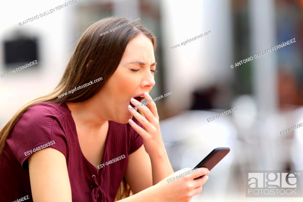 Stock Photo: Woman yawning bored with on line content holding a mobile phone sitting on a bench in the street.
