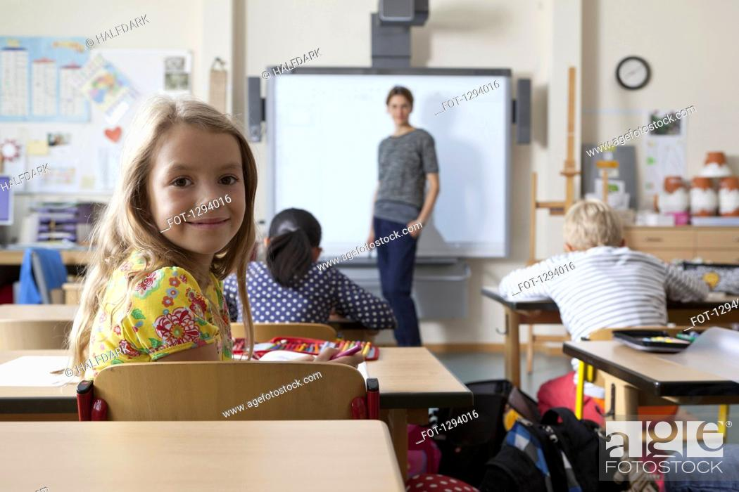 Stock Photo: Girl sitting in classroom, smiling.