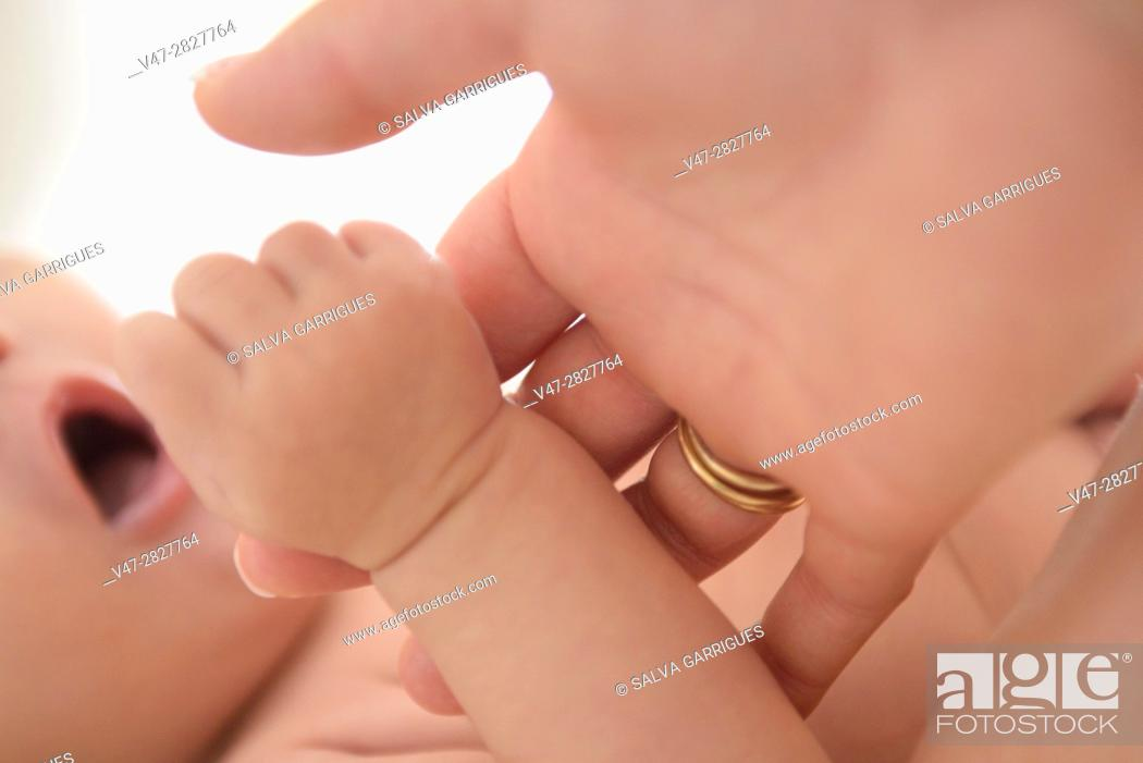Stock Photo: Baby grabs the finger of his mother's hand.