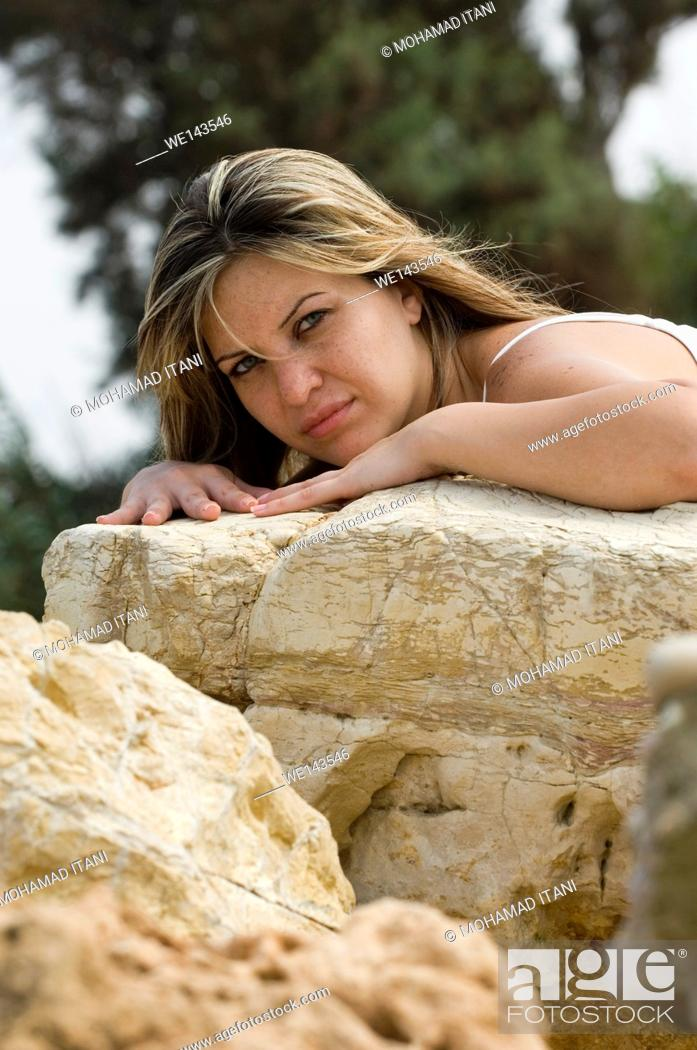Stock Photo: woman leaning on the rocks.
