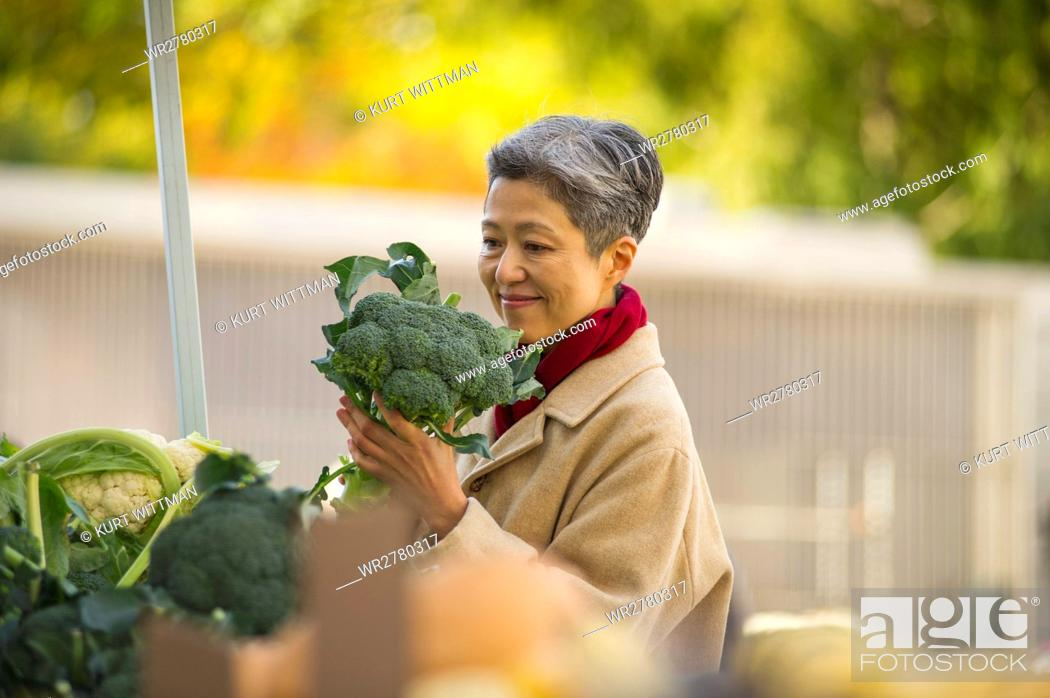 Stock Photo: Woman Shopping for Vegetables At Public Market.