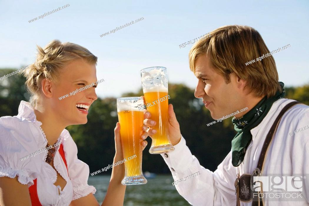 Stock Photo: Young couple in traditional Bavarian outfit, drinking beer in beer garden Munich.