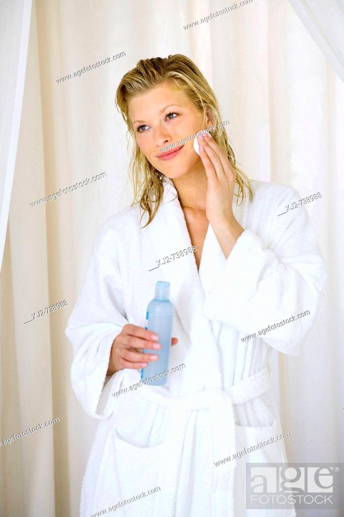 Imagen: Woman in bathrobe cleaning her face.