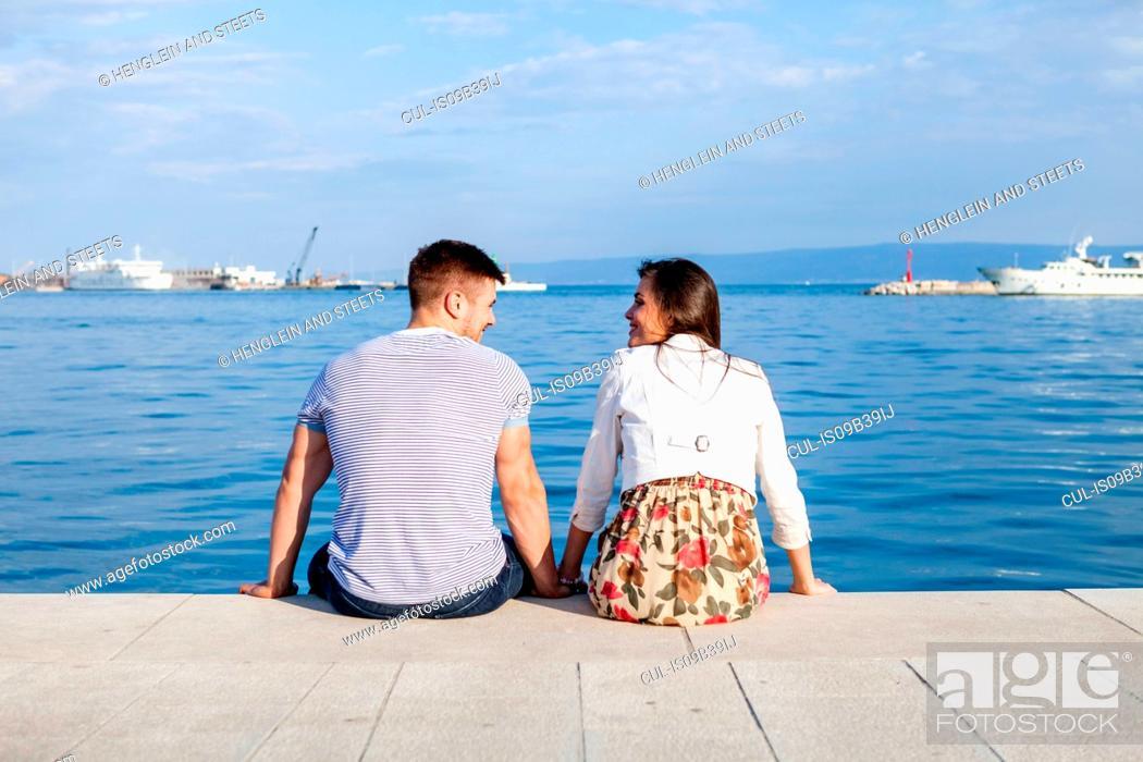 Stock Photo: Rear view of couple sitting on harbour, Split, Dalmatia, Croatia.
