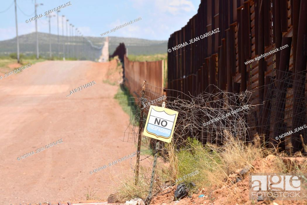Stock Photo: The international border between Naco, Arizona, USA and Naco, Sonora, Mexico is indicated by a metal wall. A sign prohibits trespassing on to private property.