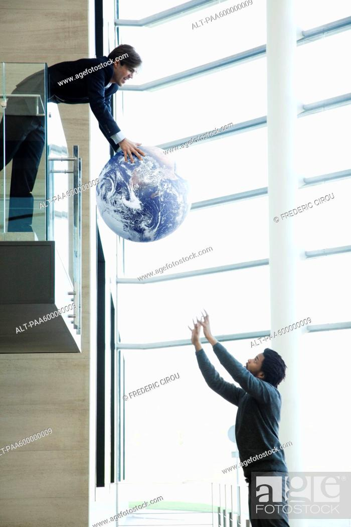 Stock Photo: Colleagues throwing ball in lobby.