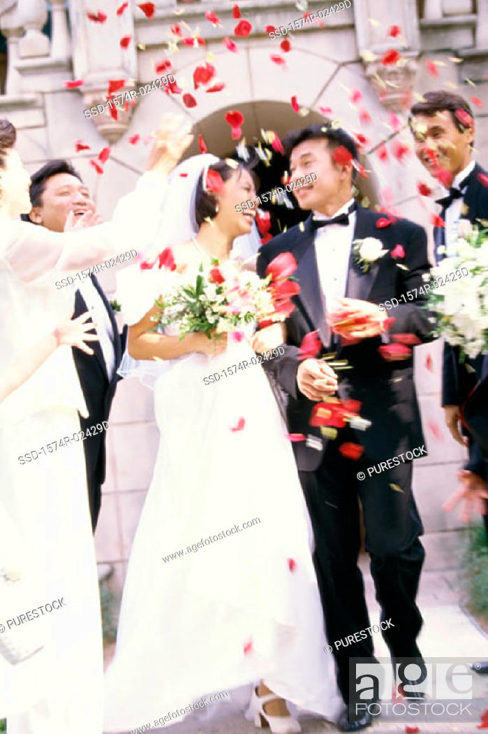 Stock Photo: Flower petals being thrown on a bride and groom.