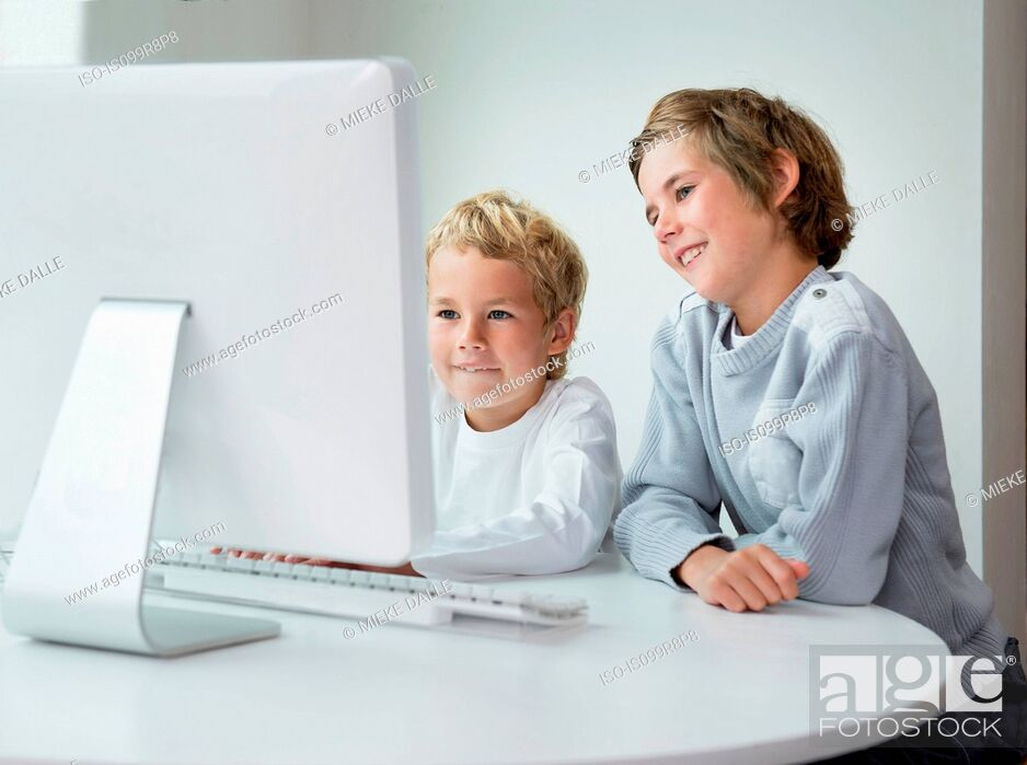 Stock Photo: Brothers looking at computer screen.
