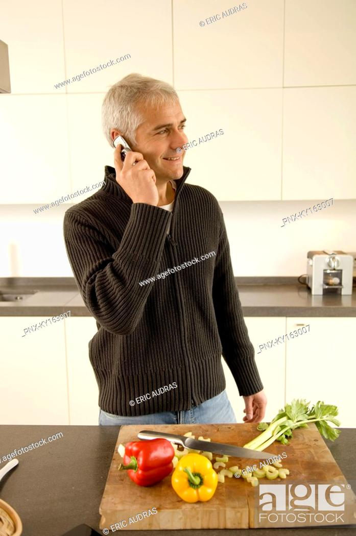Stock Photo: Mature man talking on a mobile phone in the kitchen.