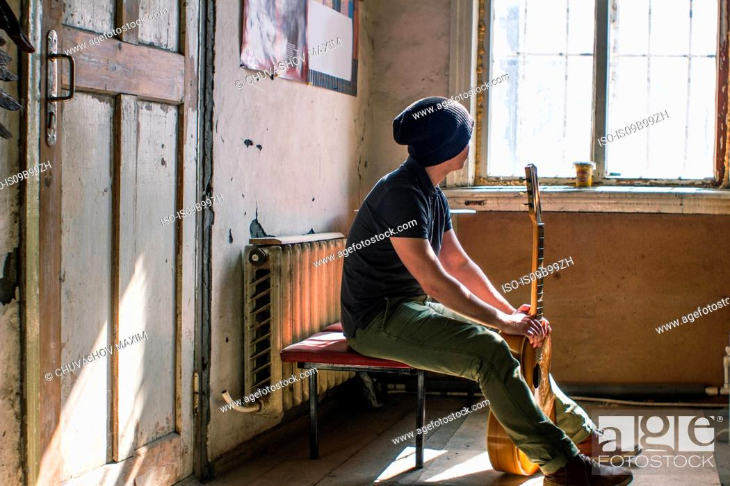 Imagen: Young man sitting on chair, holding guitar.