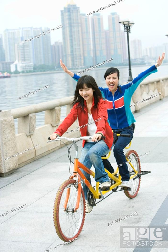 Stock Photo: Two friends riding tandem bicycle.