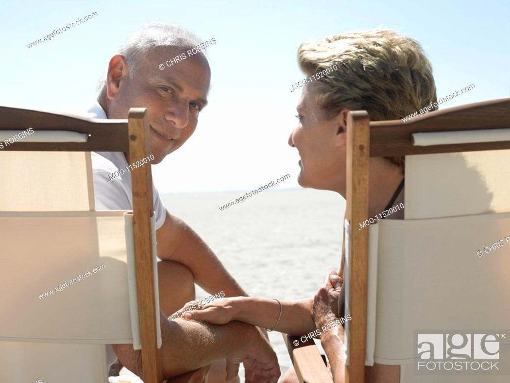 Stock Photo: Senior couple on sunloungers on beach back view.