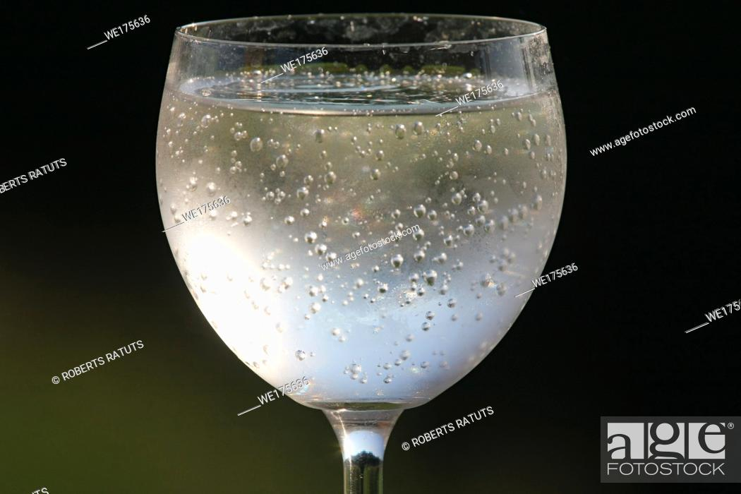 Stock Photo: Fragment of glass filled with sparkling drink in the nature. .
