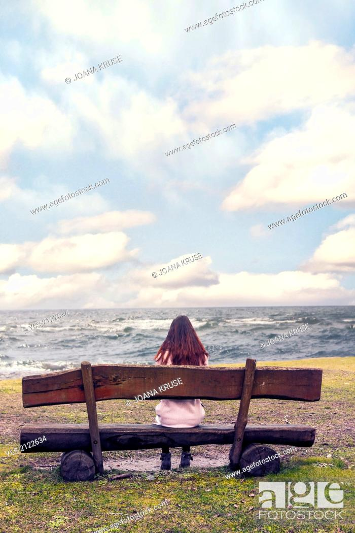 Stock Photo: a woman is sitting on a bench at the sea.